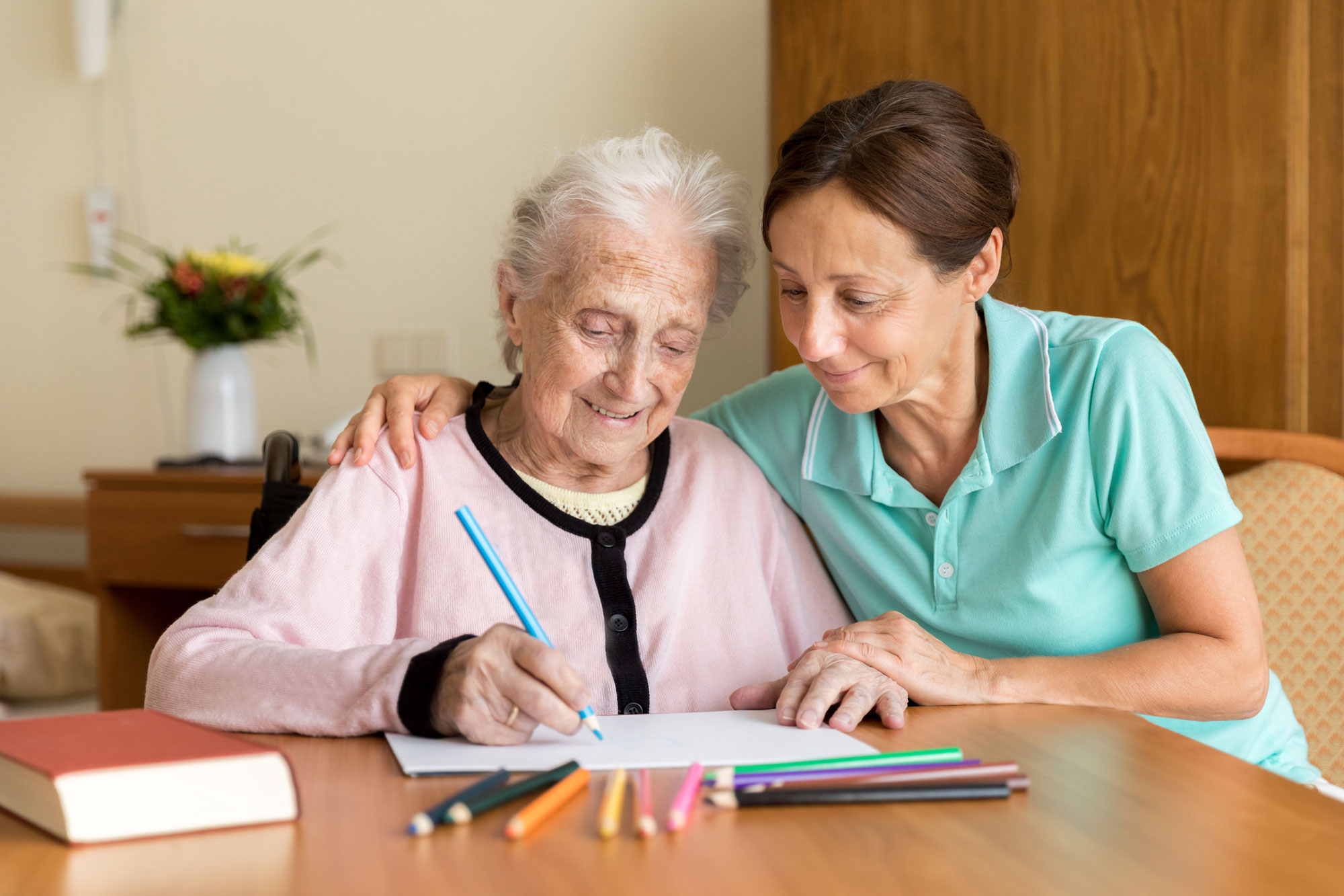 Care giver with senior woman drawing with color pencils